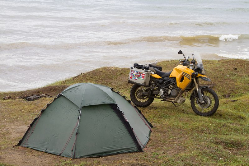 a tent and a motorcycle next to the shore