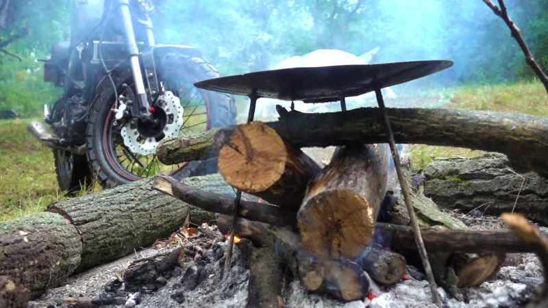 cooking food in the forest next to a motorcycle_800x450