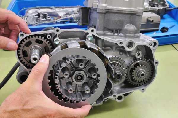 a small motorcycle engine opened and the clutch is shown