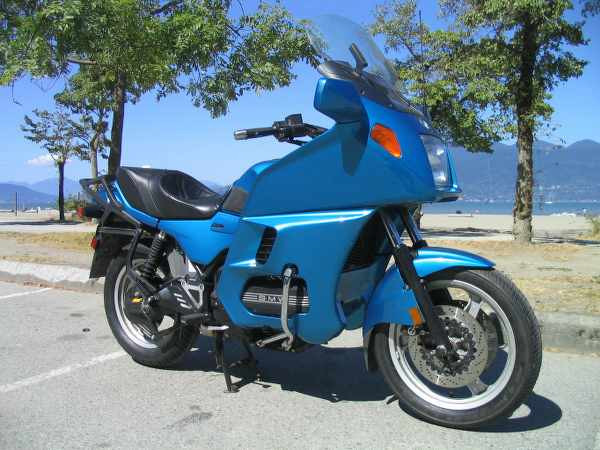 blue motorcycle in front of trees in a parking lot