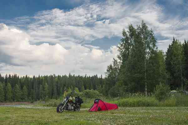 a tent and a motorcycle camping next to the forest