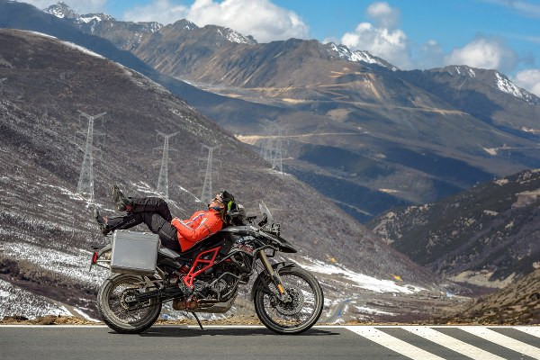 a woman on lying on a motorcycle with great natural view