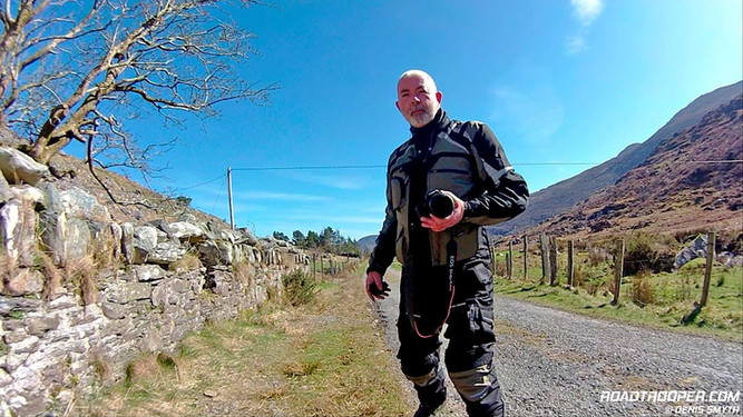 standing in the street in country side with full motorcycle gear