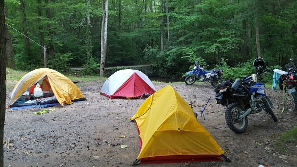 camping site with motorcycles next to tents in the forest