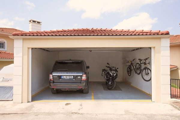 bmw 1200gs stored in a garage next to a car and bicycles