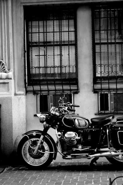 black and white classic motorcycle behind an old building