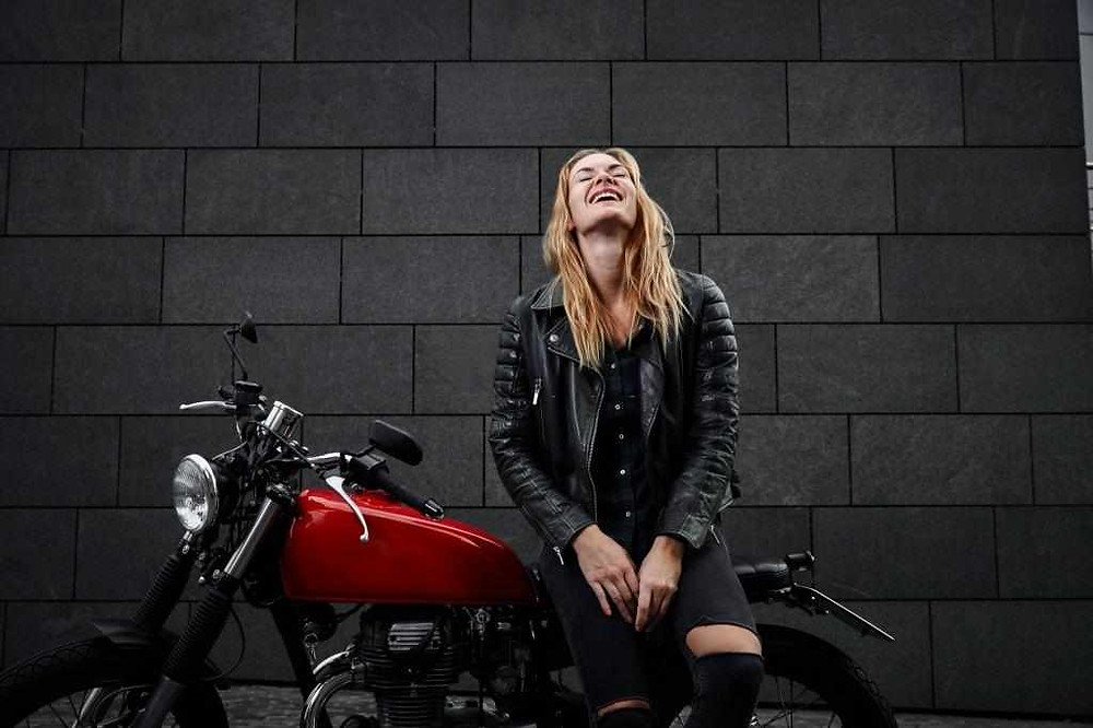 woman_motorcyclist_sitting_on_the_bike_and_laughing