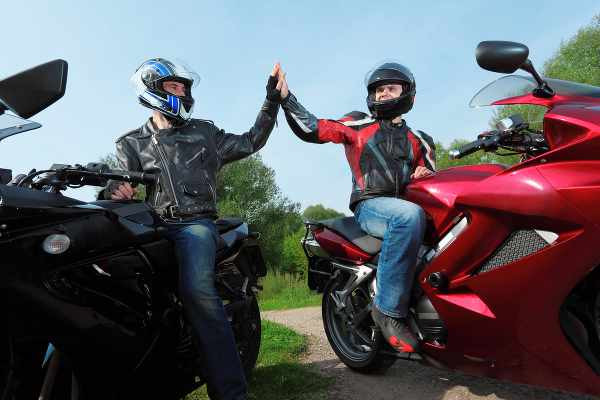 two riders giving high five to each other