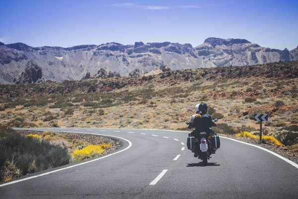 a lone rider on the road in the middle of the desert