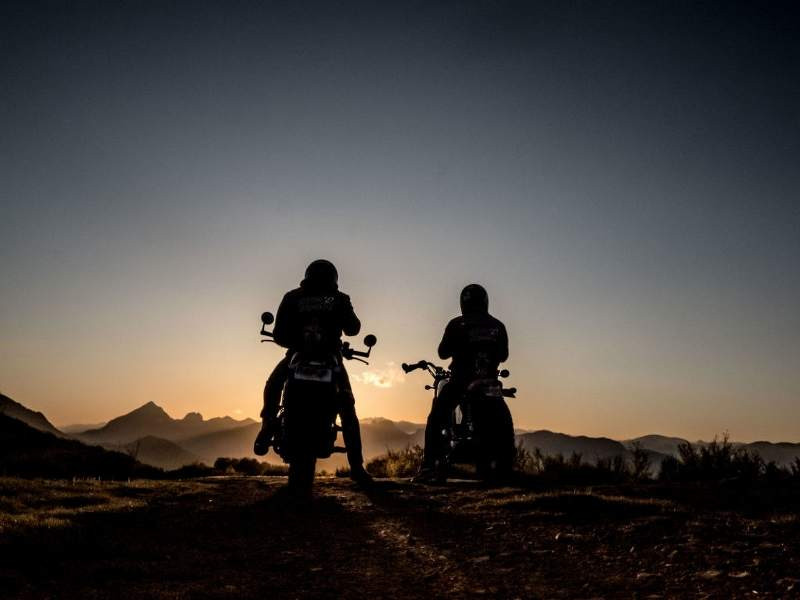 two_motorcycle_riders_in_the_off_road_looking_at_the_sunset_800x600