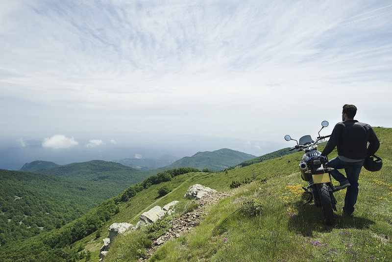 adventure_motorcyclist_standing_next_to_his_bike_admiring_view_mountains