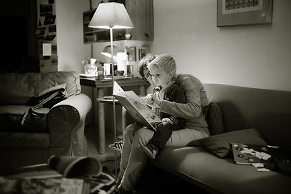 An adult reads a book to a young child