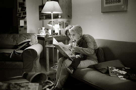 An adult reading a book to a young child