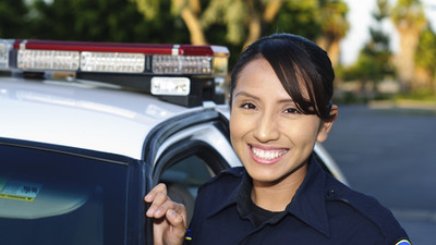 a smiling Hispanic police officer next t