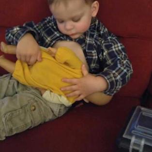 Big brother practicing baby feeding