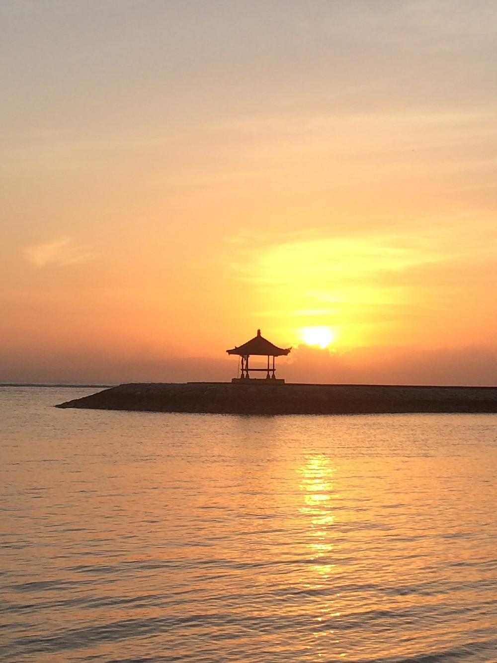Image shows a Japanese constructed house in the middle of the sea in sunset