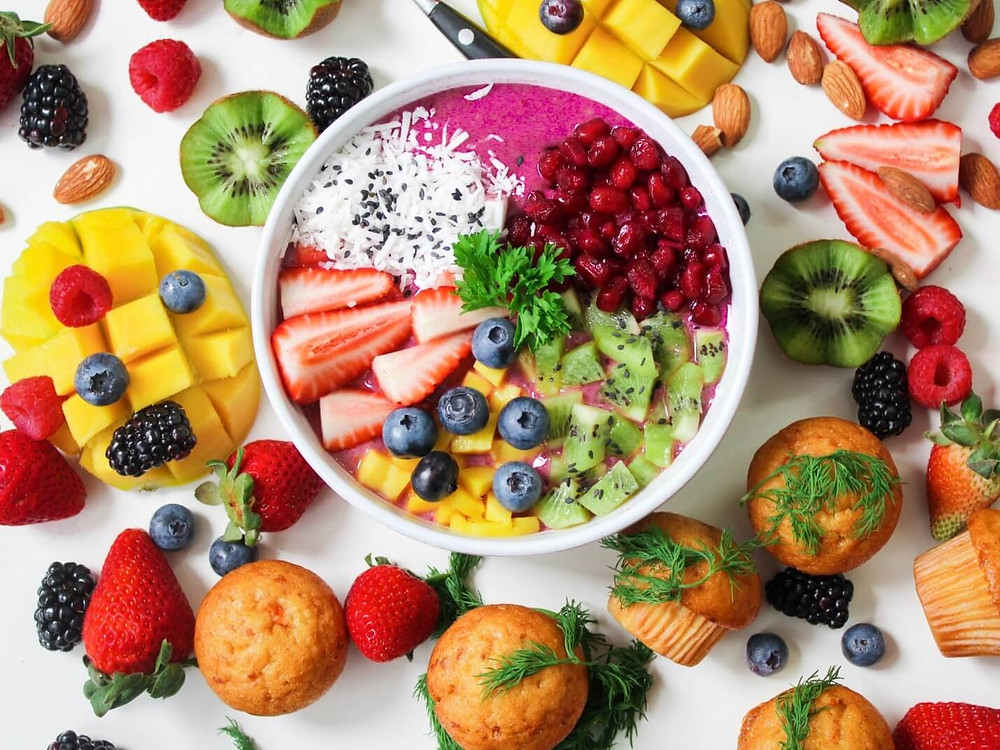 a bowl of fruits salad surrounded by other fruits and muffins
