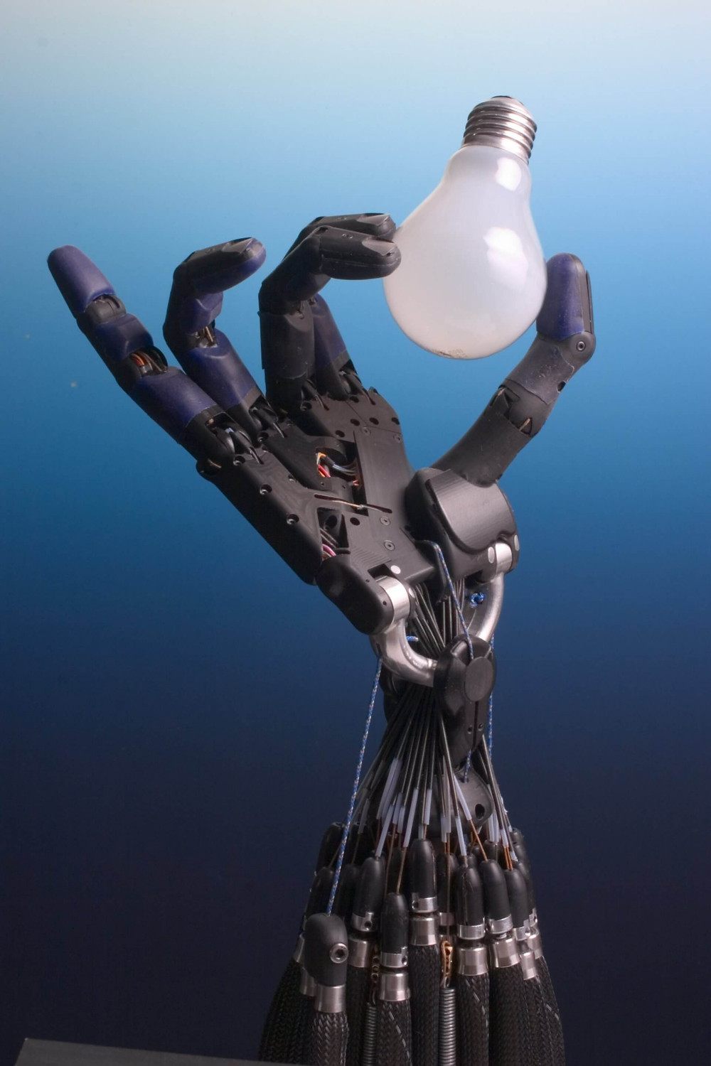 The Shadow robot hand system holding a glass light bulb