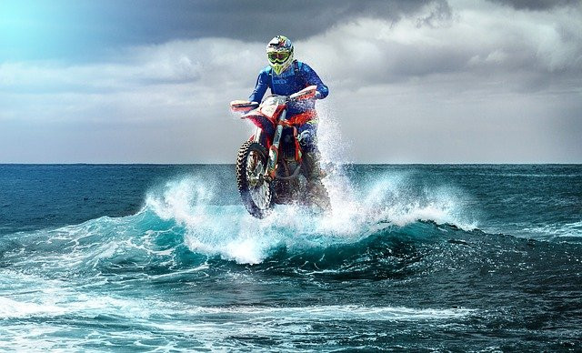 man riding a motocross bike on water, blue waves an cloud in the background
