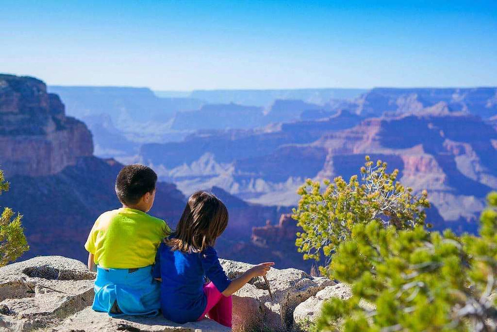 Two kids sitting on the rock looking at a beautiful mountain landscape