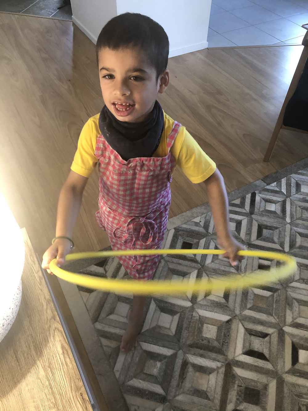 KEANU a young boy playing with a yellow hula hoop on a grey and white triangle patterned rug.
