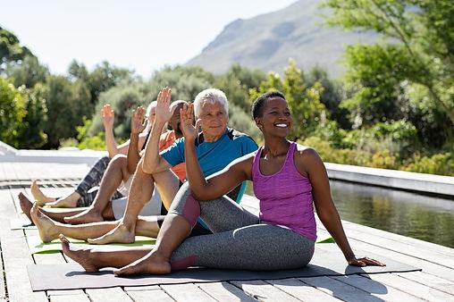 Senior men and mature women doing yoga exercise near swimming pool outdoor.Multiethnic pe