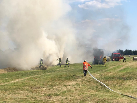 Rundballenpresse auf Feld in Brand geraten