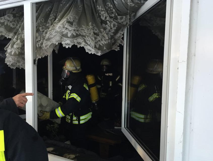 Einsatzkräfte tragen verbrannte Möbel und Geräte aus dem Zimmer
