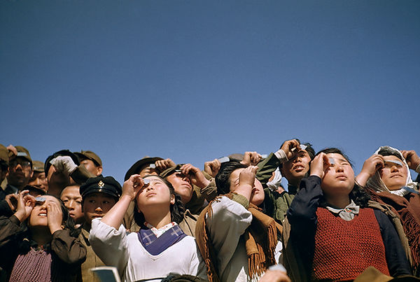 People watching a solar eclipse squint t