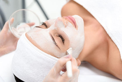Woman in white headband receiving clay mask facial with brush from esthetician