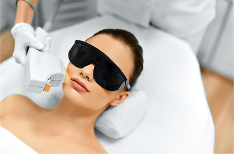 Woman receiving Lightstim treatment on cheek with sunglasses, by esthetician in white gloves