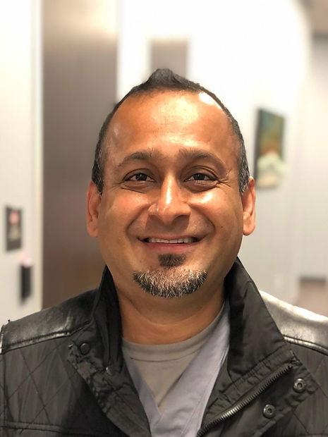 Headshot of Dr Jogesh Harjai, smiling in jacket