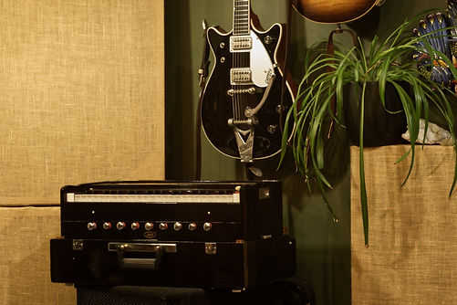 JAS Musicals Harmonium and a guitar hanging on a wall. It is a Gretsch Duo Jet 1962 reissue in black. A spider plant is also visible.