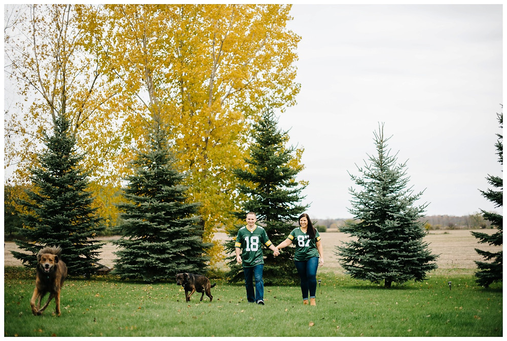 couple-walking-with-dogs-at-green-bay-engagement-session-by-appleton-wedding-photographer-kyra-rane-photography