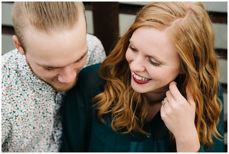 husband-and-wife-sitting-on-bridge-laughing-at-anniversary-session-at-high-cliff-state-park-by-appleton-wedding-photographer-kyra-rane-photography