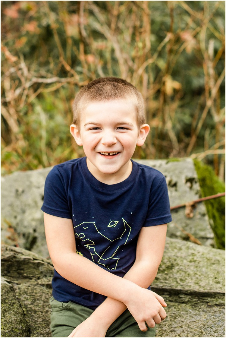 little-boy-sitting-on-a-rock-smiling-at-camera-at-family-session-in-the-great-smoky-mountains-by-appleton-wedding-photographer-kyra-rane-photography