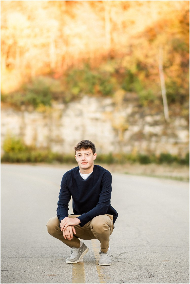 boy-sitting-in-middle-of-road-at-senior-session-at-high-cliff-state-park-by-milwaukee-wedding-photographer-kyra-rane-photography