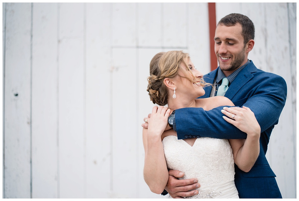grooms-arms-wrapped-around-bride-at-brighton-acres-wedding-by-green-bay-wedding-photographer-kyra-rane-photography