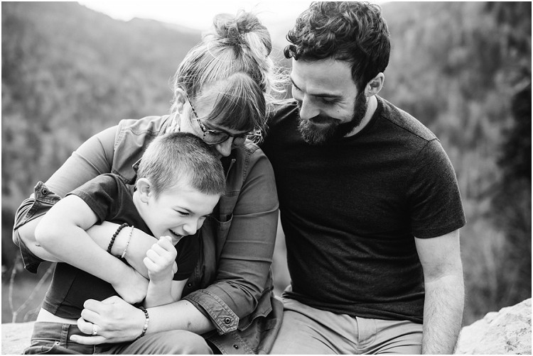 family-sitting-on-rock-ledge-snuggled-close-at-family-session-in-the-great-smoky-mountains-by-green-bay-wedding-photographer-kyra-rane-photography