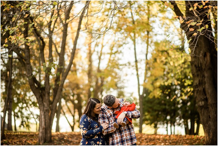 family-standing-under-trees-with-baby-at-plamann-park-by-appleton-wedding-photographer-kyra-rane-photgraphy