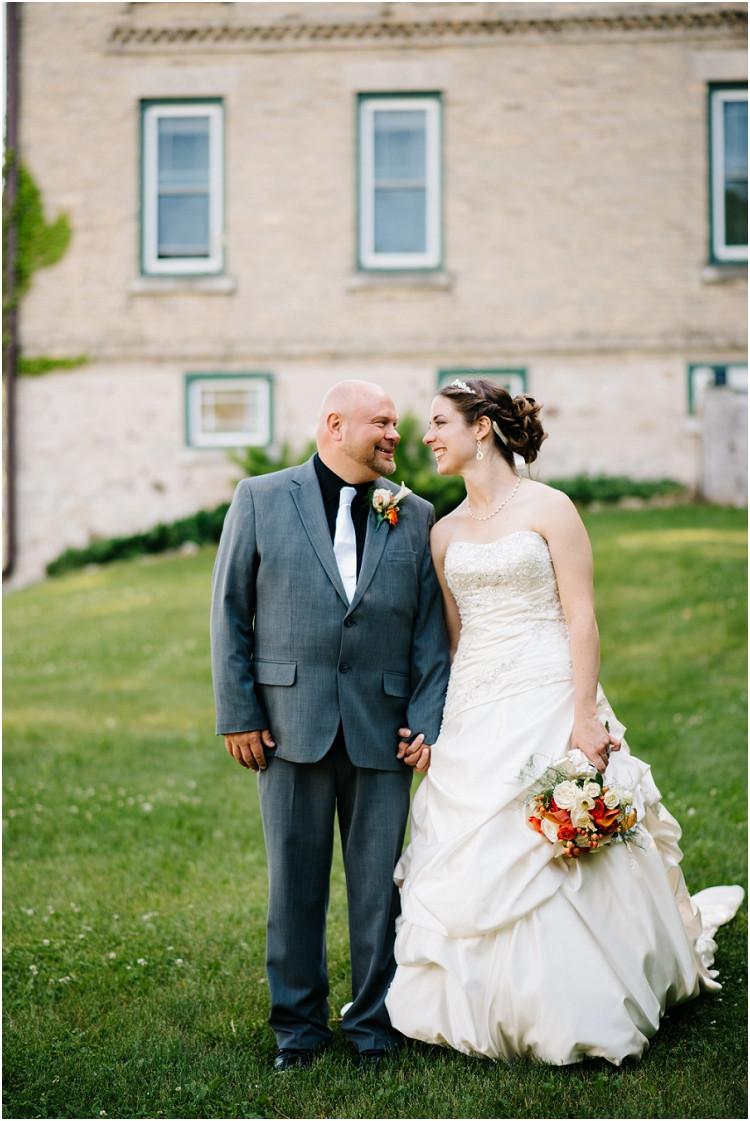 wedding-couple-smiling-holding-hands-at-wisconsin-farm-wedding-by-appleton-wedding-photographer-kyra-rane-photography