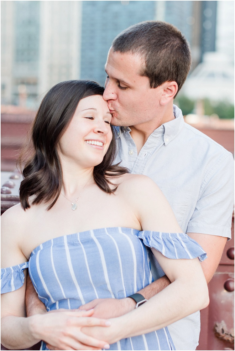 husband-kissing-wifes-forehead-on-walking-bridge-at-downtown-chicago-anniversary-session-by-green-bay-wedding-photographer-kyra-rane-photography