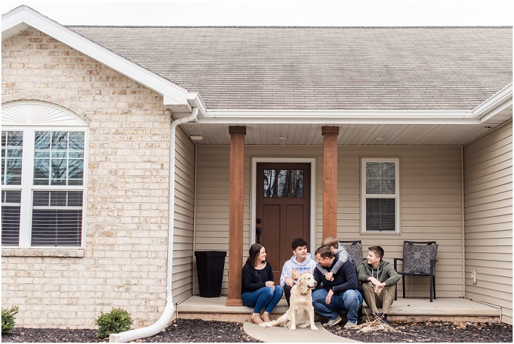 family-on-front-porch-laughing-with-dog-at-the-front-porch-series-by-appleton-wedding-photographer-kyra-rane-photography