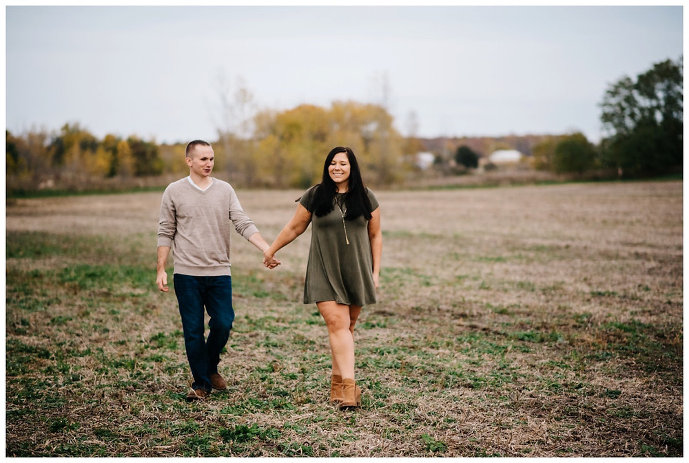 engaged-couple-walking-in-field-at-green-bay-engagement-session-by-appleton-wedding-photographer-kyra-rane-photography