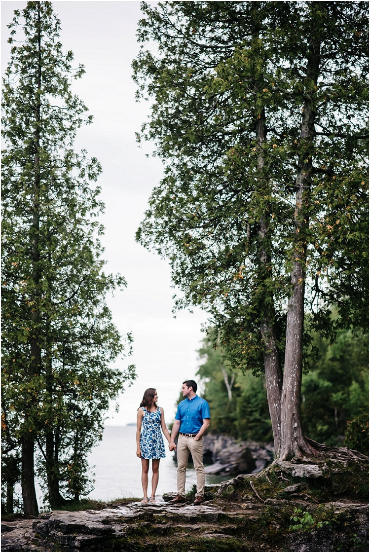 engaged-couple-holding-hands-on-cliff-at-cave-point-engagement-session-by-milwaukee-wedding-photographer-kyra-rane-photography