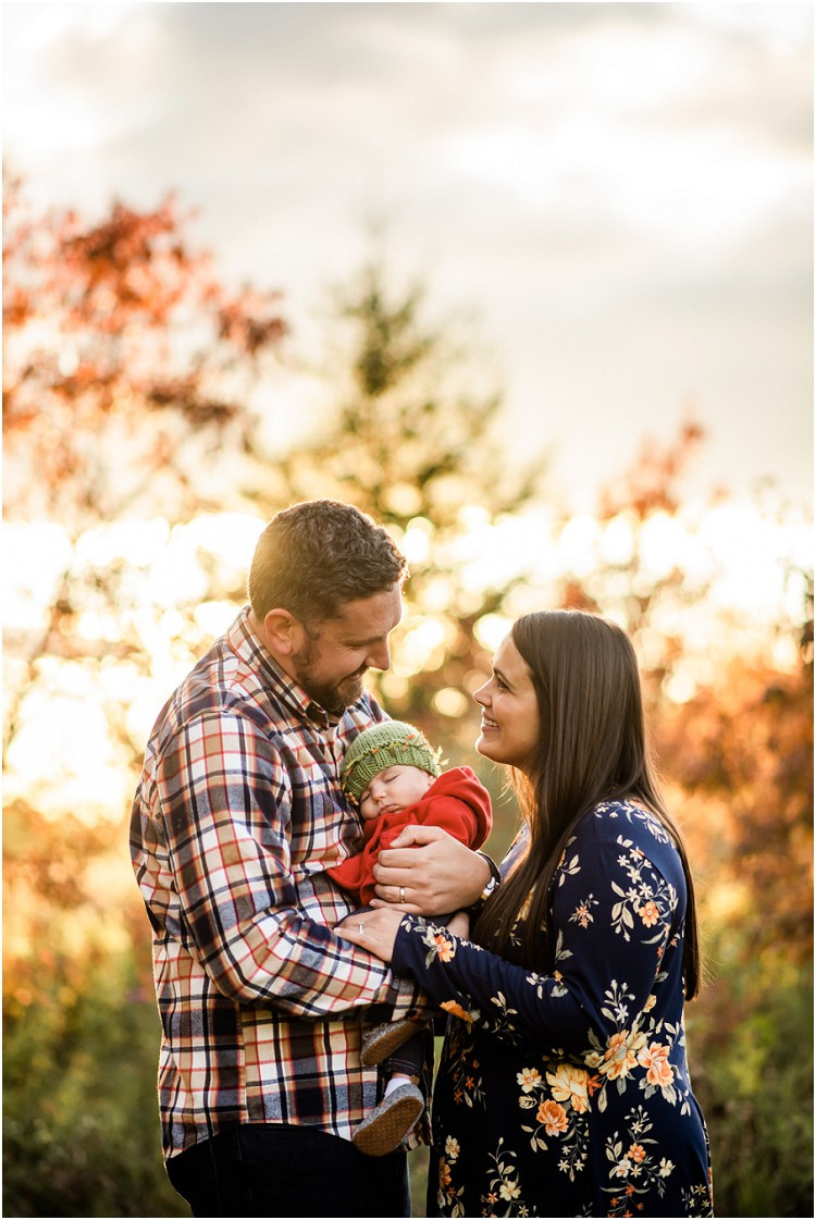 mom-and-dad-holding-sleeping-baby-looking-at-each-other-at-plamann-park-by-appleton-wedding-photographer-kyra-rane-photgraphy