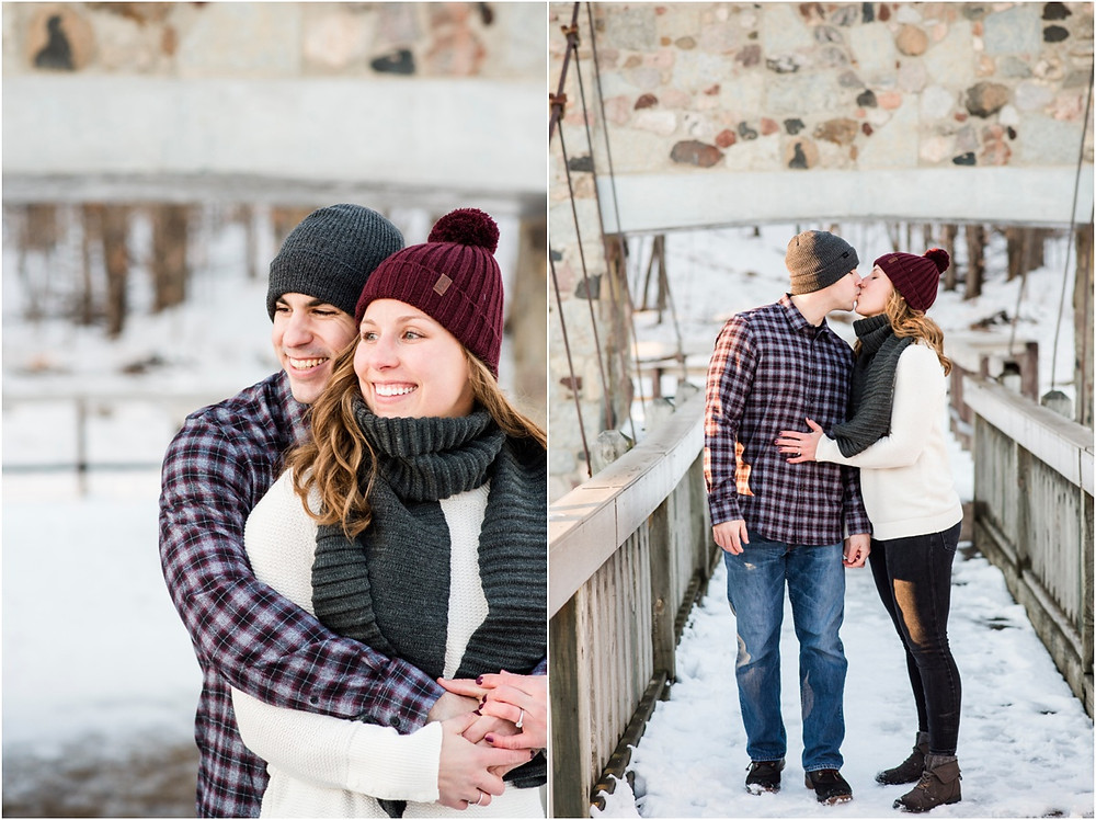 engaged-couple-smiling-on-bridge-holding-hands-at-pamperin-park-winter-engagement-session-by-milwaukee-wedding-photographer-kyra-rane-photography
