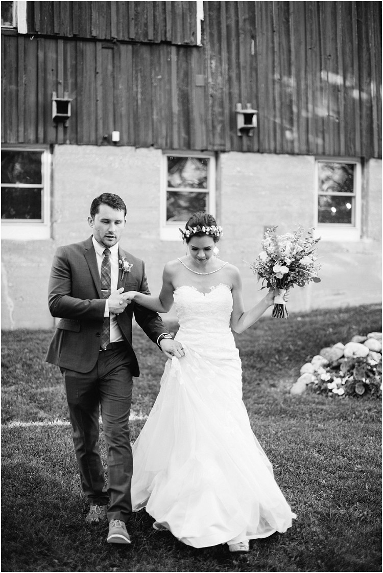 groom-holding-brides-dress-at-barnsite-retreat-and-events-wedding-by-milwaukee-wedding-photographer-kyra-rane-photography