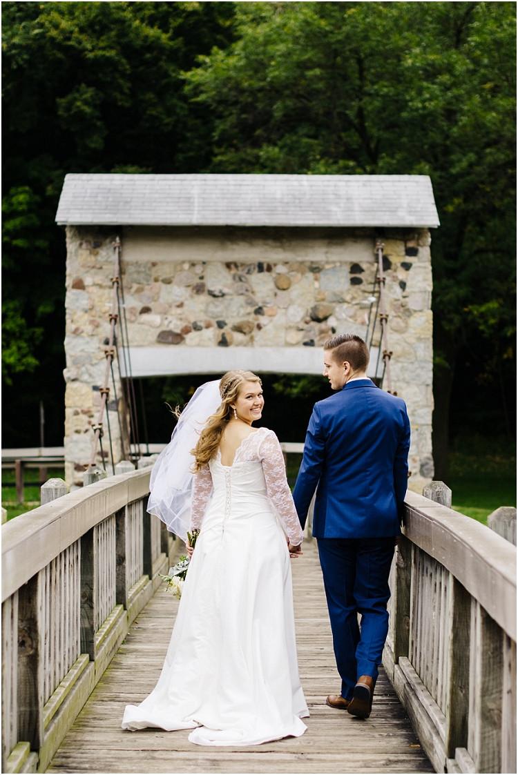 wedding-couple-walking-on-bridge-bride-looking-back-at-pamperin-park-wedding-by-green-bay-wedding-photographer-kyra-rane-photography
