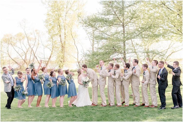 wedding-party-celebrating-while-bride-and-groom-kiss-at-minnesota-wedding-by-appleton-wedding-photographer-kyra-rane-photography